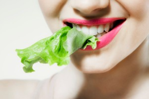 Young woman biting lettuce-Healthy Care